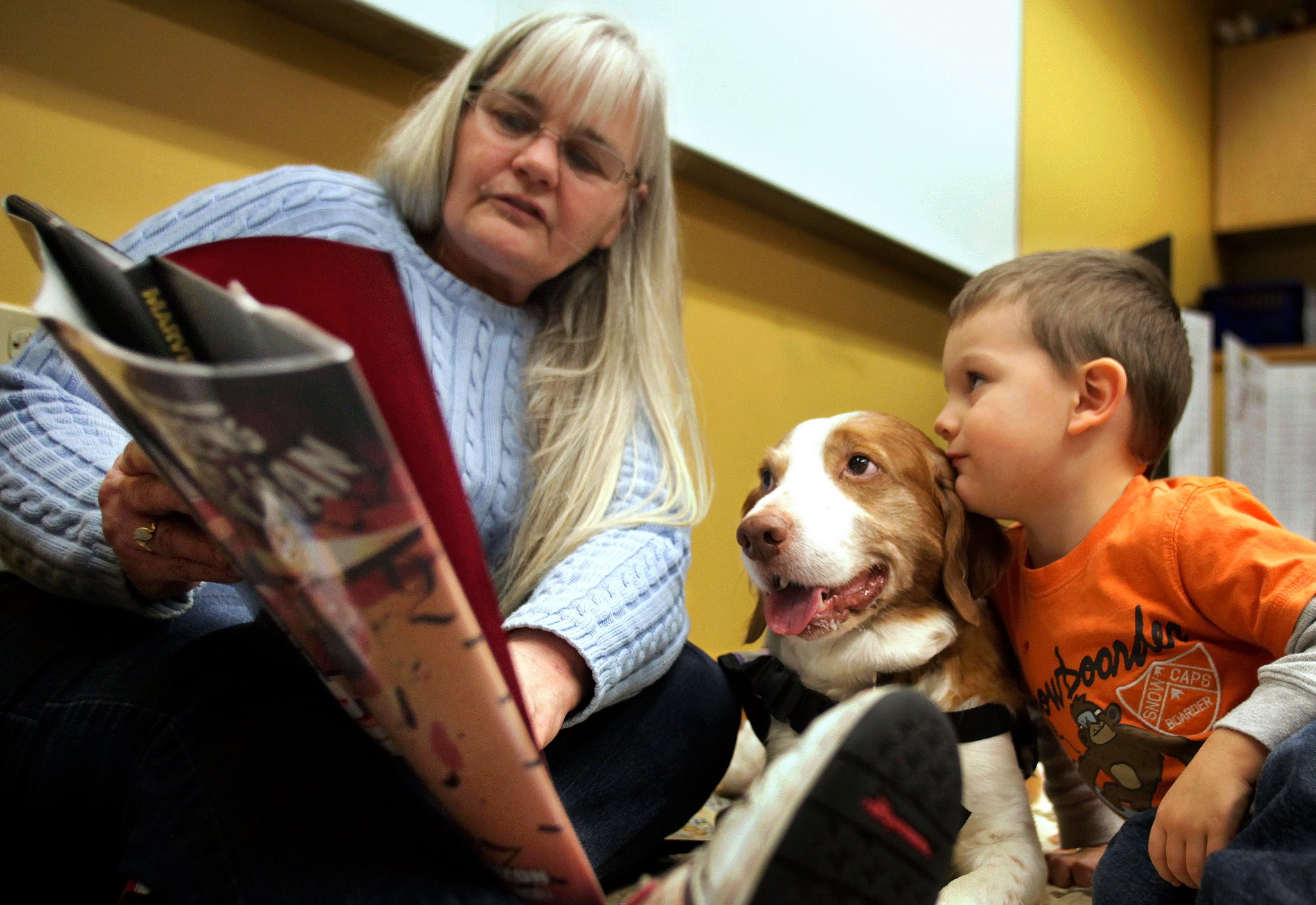 Photo of an adult reading to a child and dog.