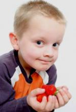Photo of a preschooler holding onto a red toy.