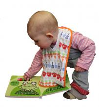 Photo of a baby bending down to play with a book.