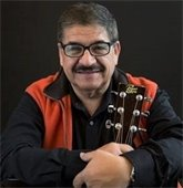 Photo of musician Marco, who is wearing red and black and holding a guitar