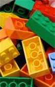 Photo of plastic building bricks in yellow, orange, green, and red