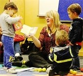 Photo of staff, parents, and children enjoying books together at storytime