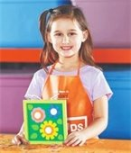 Photo of child wearing home depot apron and holding a colorful creation