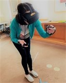 Photo of woman wearing VR headset and hand controls