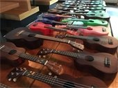 Photo of multiple ukuleles in varied colors displayed on a table