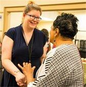 Staff member Carol shakes Carla Hayden's hand