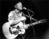 Black and white photo taken in 1986 of musician Pete Seeger on stage with guitar. Photo by Josef Schwarz.