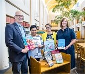 Photo of Rick Larsen, Carla Hayden, Cassie Franklin, and Abby Cooley accepting a gift of books from the Library of Congress