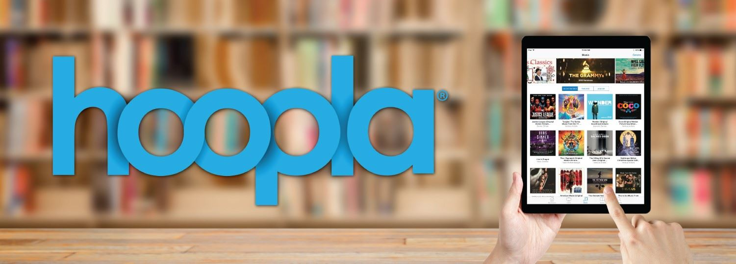 the hoopla logo in blue next to a picture of a person using a tablet to access hoopla