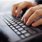 Photo of hands typing on computer keyboard