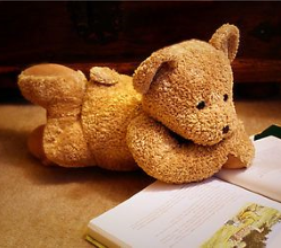 Teddy bear posed as if he is reading a book.
