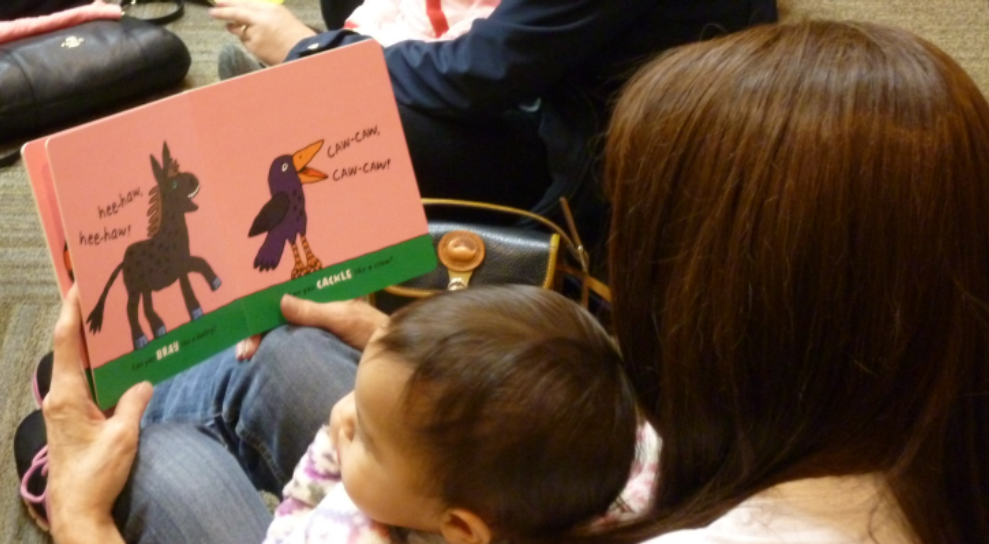Photograph of family reading a board book together.