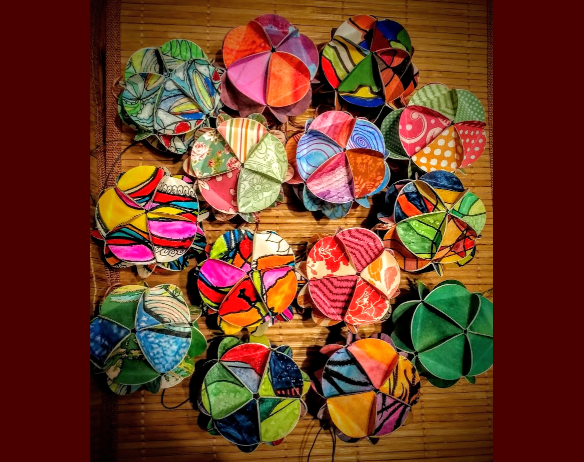 Photo of colorful 12 sided paper ornaments made from recycled artwork