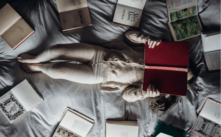 Girl reading a book on a bed, surrounded by many books