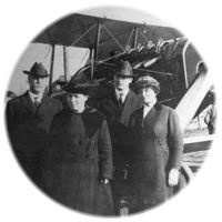 Circular black and white photo of 2 men and 2 women in front of an airplane