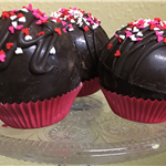 Picture of three hot chocolate bombs with heart sprinkles.