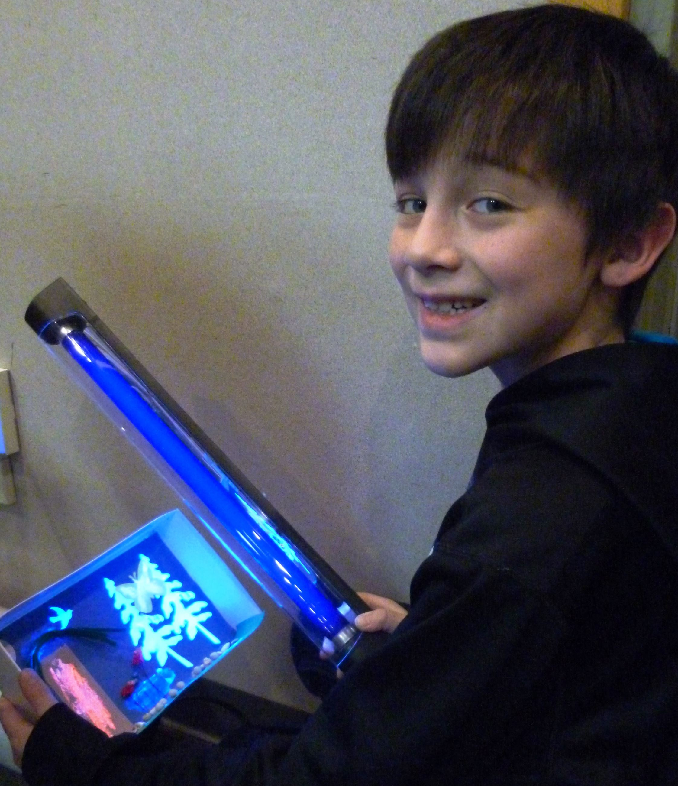 Boy holding a glowing naturescapes art creation and a black light