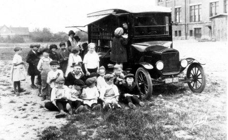 1924 black and white photo of the Pegasus bookmobile parked in the grass with a group of children