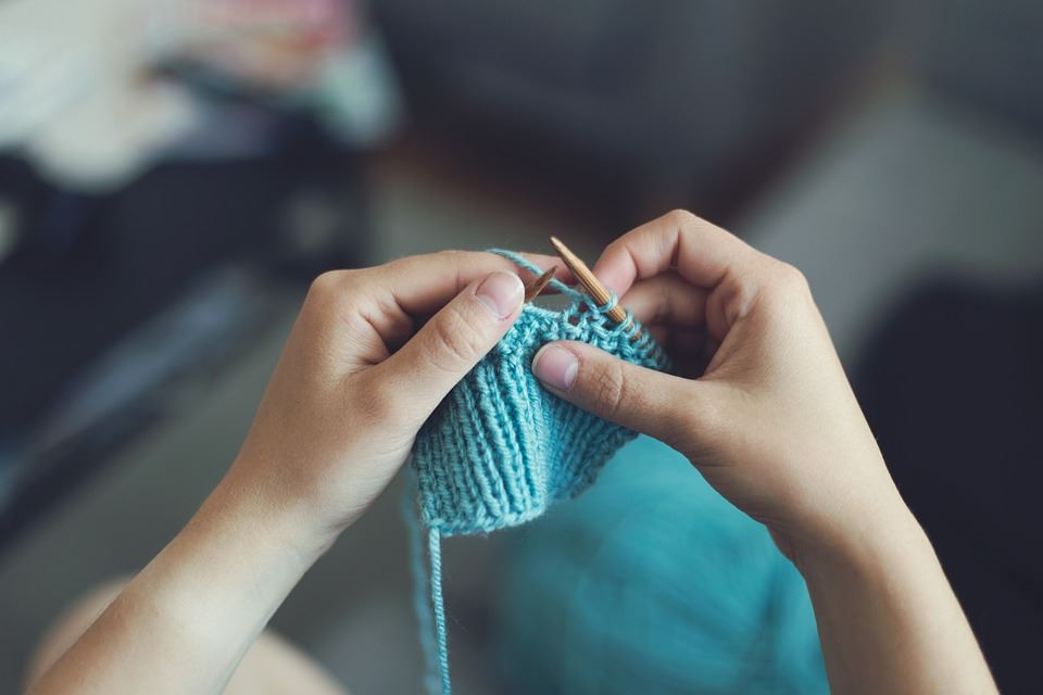 Photo of someone knitting with teal colored yarn