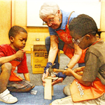 Photo of two boys building with a Home Depot staff member.