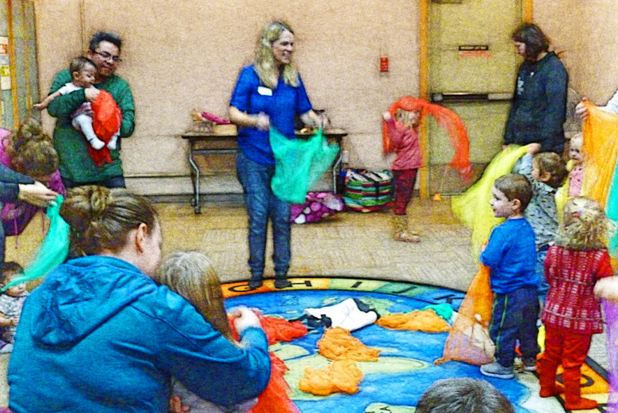 Families playing with colorful scarves during Music and Movement Storytime.