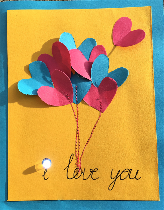 Handmade card with paper hearts, and an LED light dotting the i in I love you