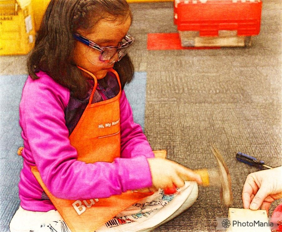 Photograph of a child using a hammer wearing safety goggles and a Home Depot apron