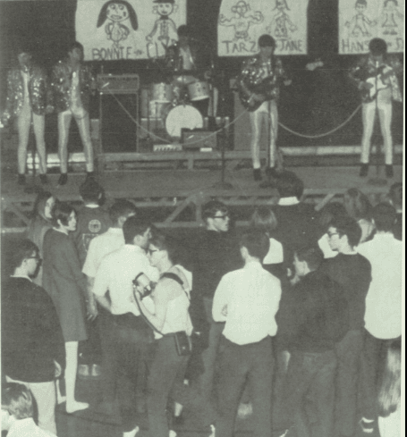 Black and white photograph. In the foreground there are a group of teenagers facing a stage. One gir