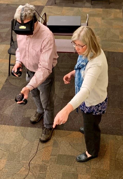 a woman points at a screen while talking to a man wearing a VR headset and using 2 VR controllers