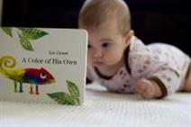 Photo of baby looking at a book.